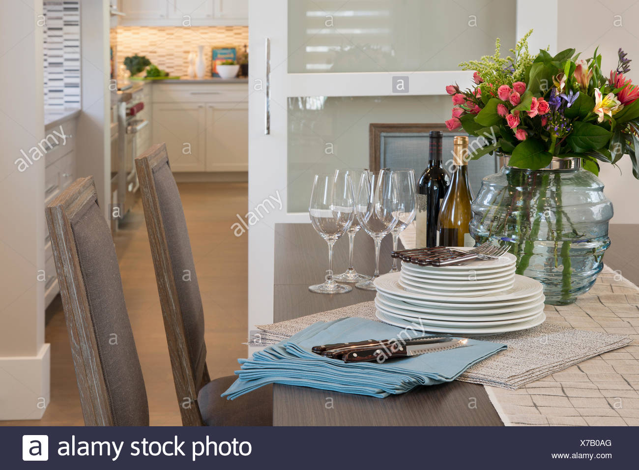 Blumenstrauß und gestapelten Maßgedecke Esstisch Stockbild