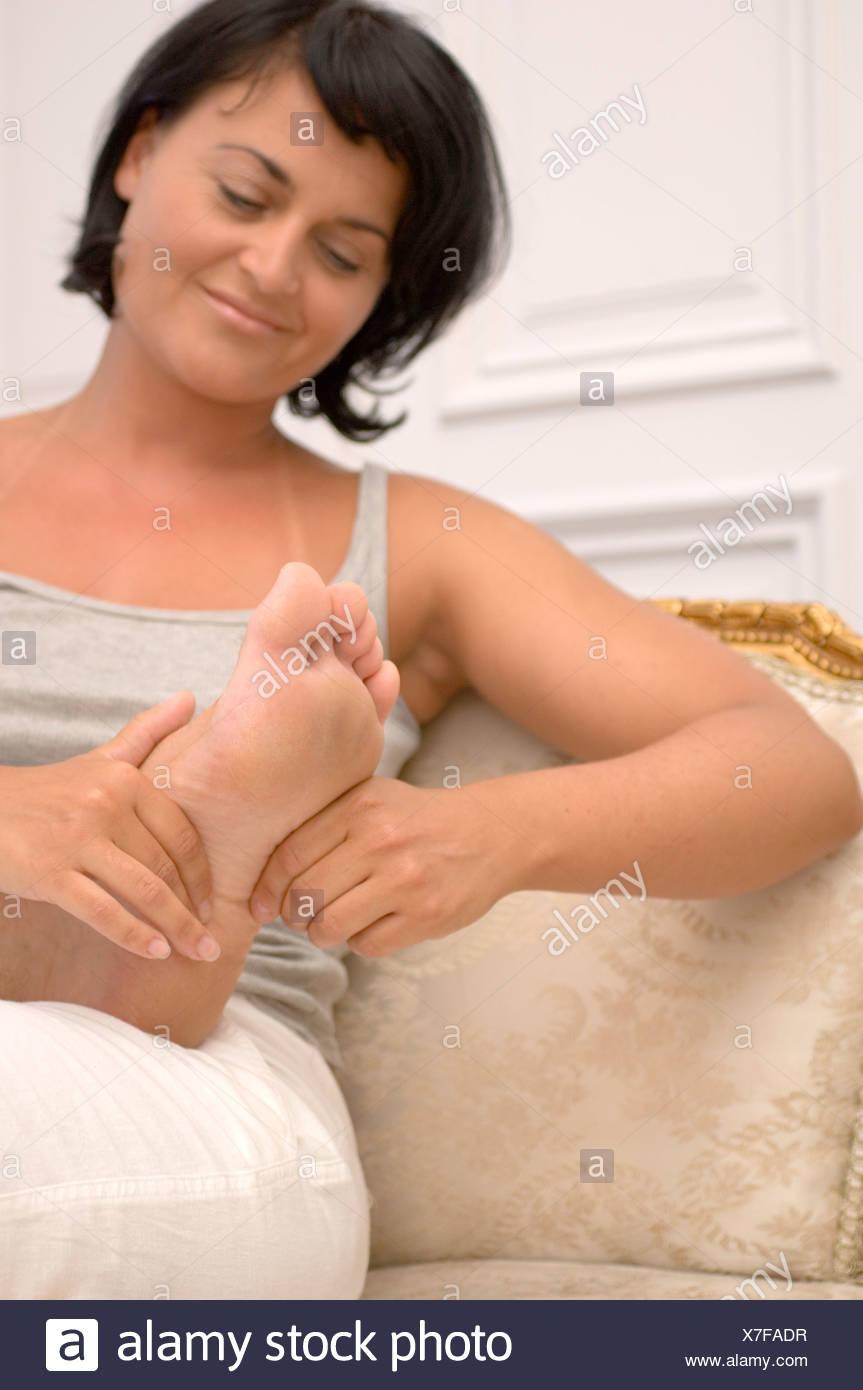 Eine Frau, die ihrem Partner eine Fußmassage geben Stockbild