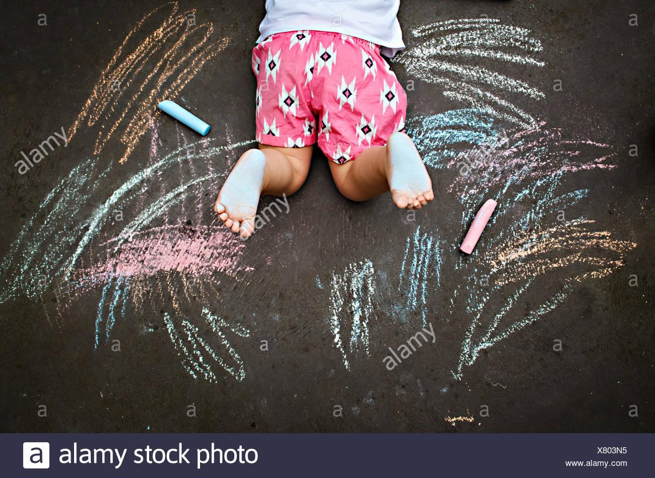 Draufsicht des Mädchens auf Boden mit Kreide zeichnen Stockbild