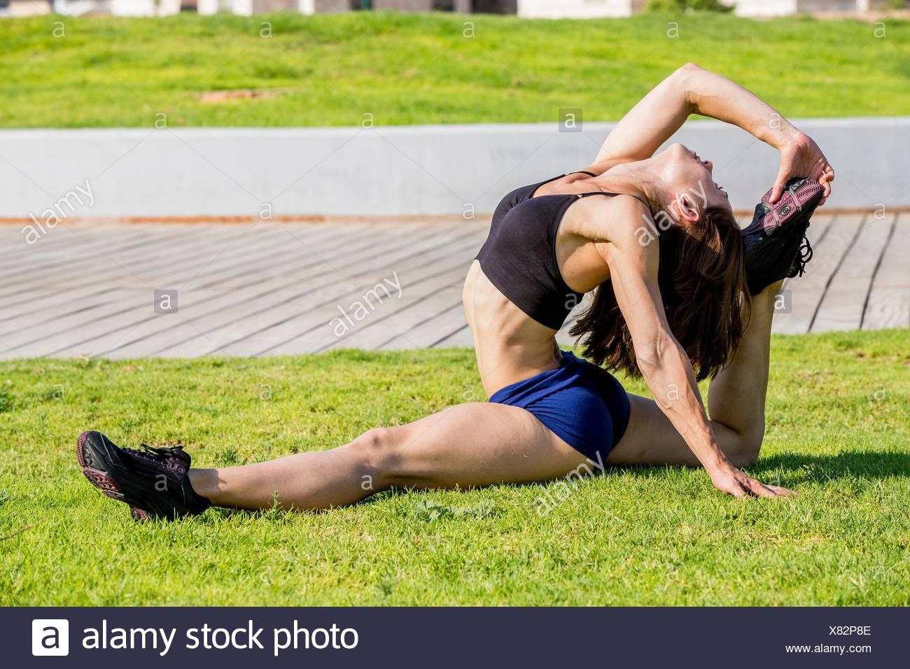 Junge Frau tut erstreckt sich im park Stockbild