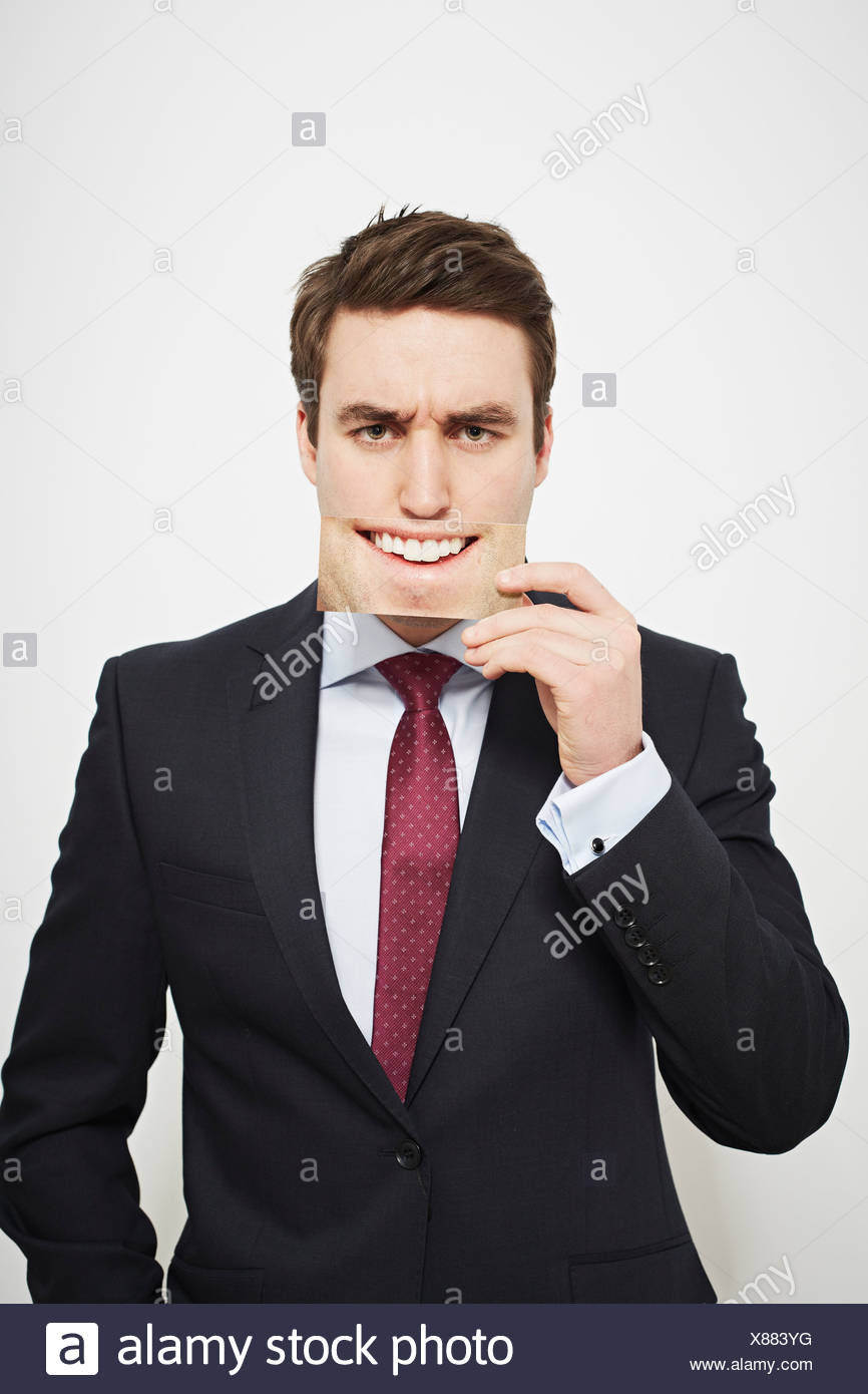 Geschäftsmann hält böse Bild über sein Gesicht Stockbild