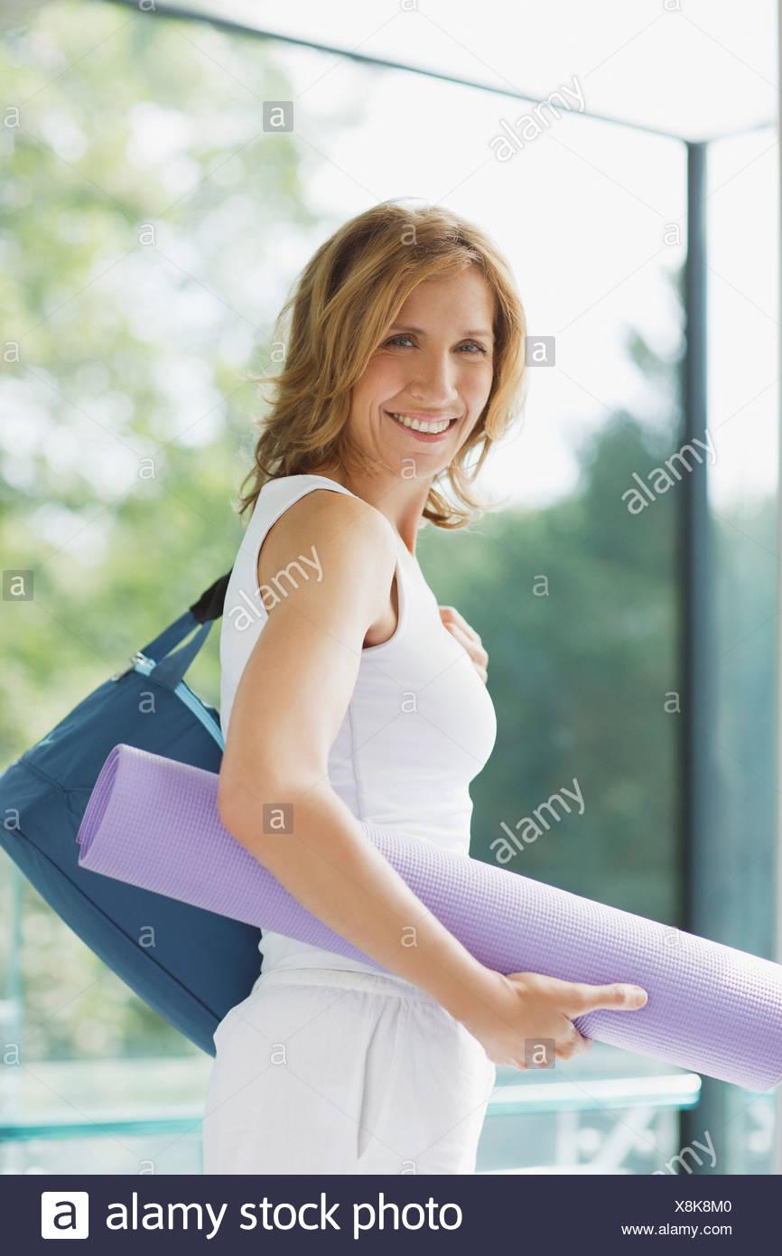 Lächelnde Frau hält Yoga-Matte Stockbild