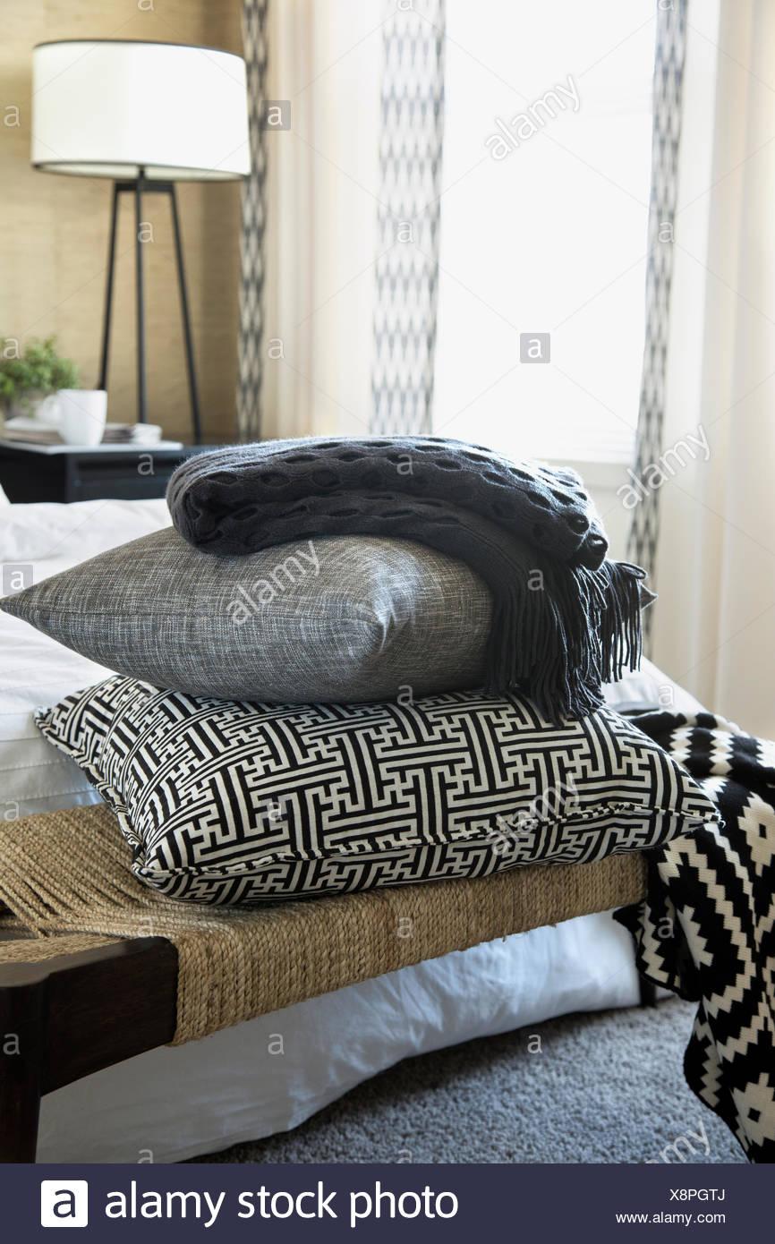 Kissen und Decke gestapelt auf Bank im Schlafzimmer Stockbild