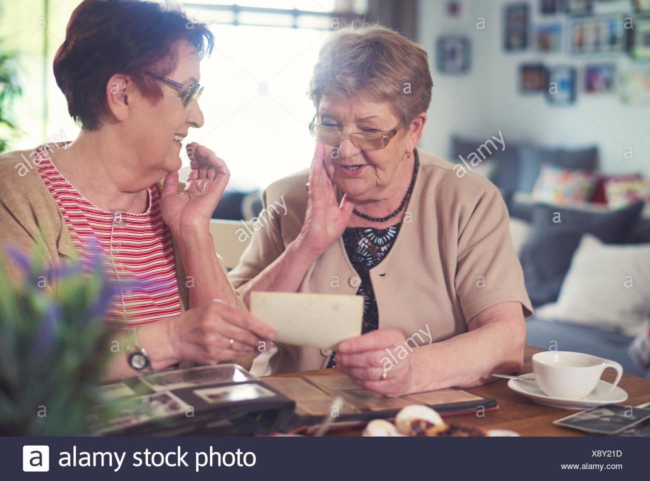 Zwei alte Frauen plaudern beim Betrachten von Alter Fotografien am Tisch Stockbild
