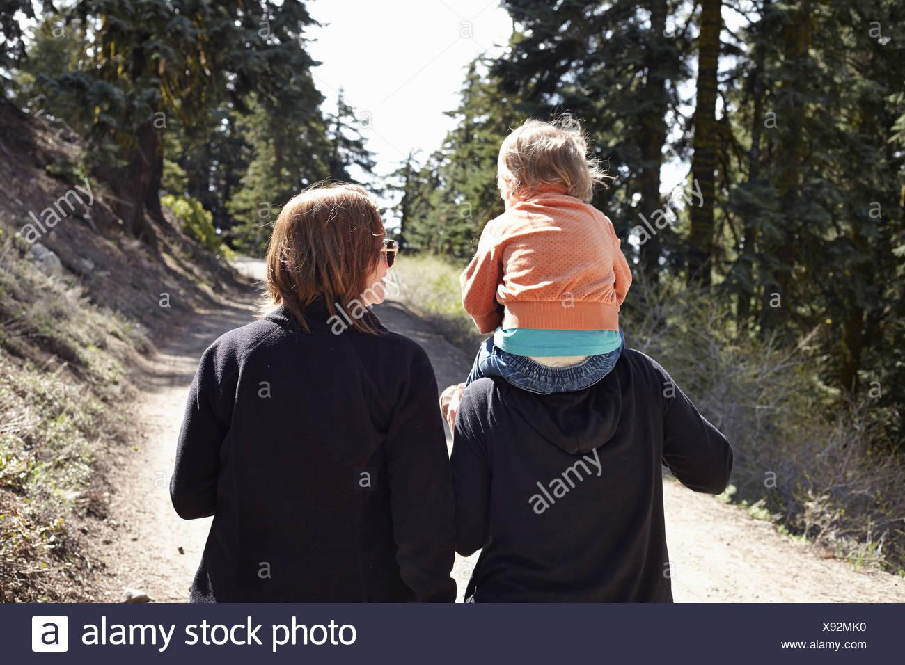 Frauen, die zu Fuß durch Wald in Oregon, USA, mit Kleinkind auf Schultern sitzen Stockbild