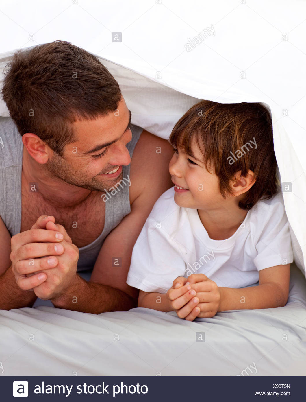 Vater und Sohn sprechen unter der Bettwäsche Stockbild