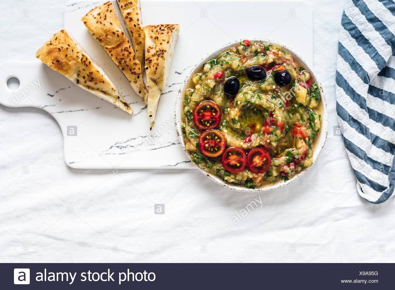 Baba Ganoush gemacht mit gebratene Auberginen, Paprika und Kräutern aber kein Tahini auf eine Tafel aus Draufsicht fotografiert. Pita-Scheiben sind auf dem s Stockbild