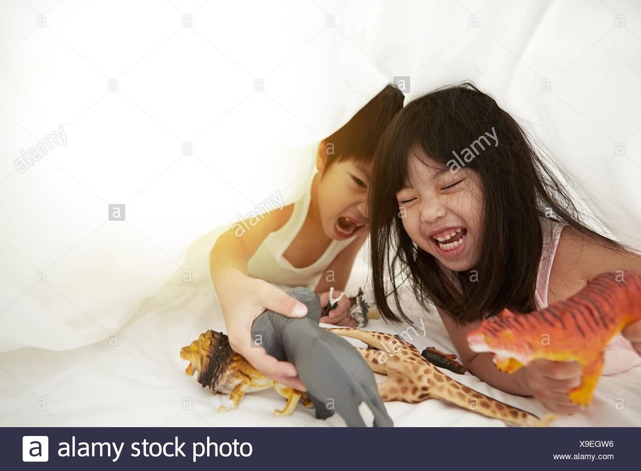 Chinesischen jungen und Mädchen im Bett spielen mit ihren Spielsachen unter der Bettwäsche Stockbild