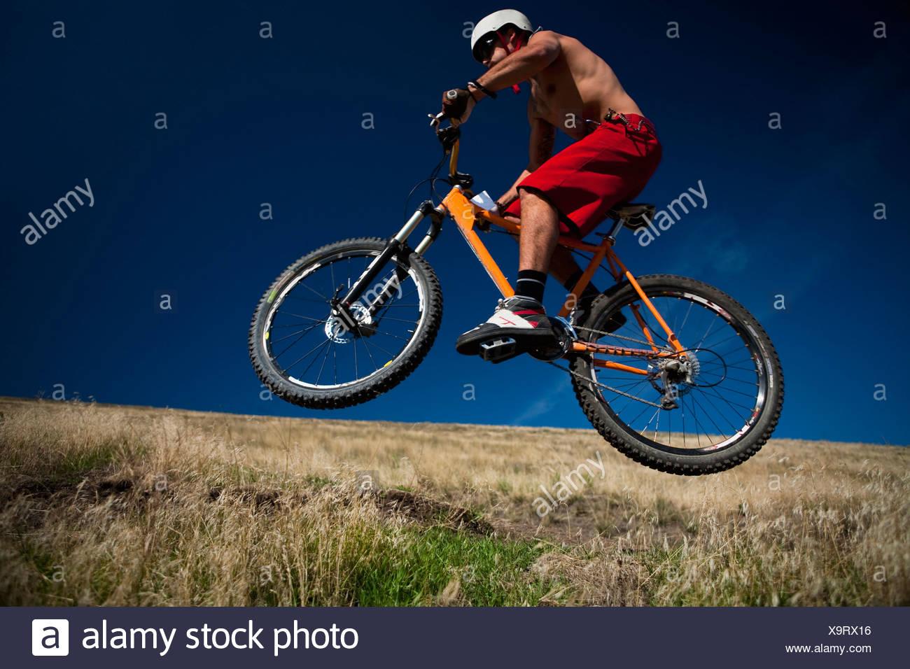 Ein männliche Mountainbiker wird Luft während der Fahrt einer Strecke auf Mt. Sentinel, Missoula, Montana. Stockbild
