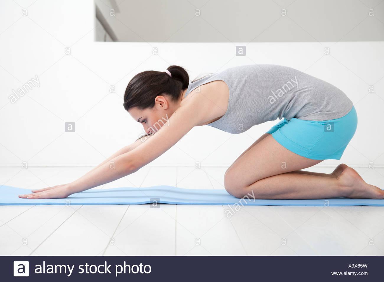 Frau erstreckt sich auf Yoga-Matte Stockbild