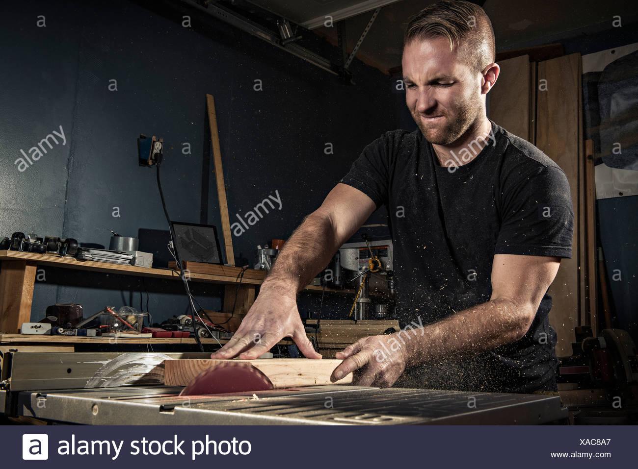 Männliche Zimmermann mit einem Rotary sah in Werkstatt Stockbild