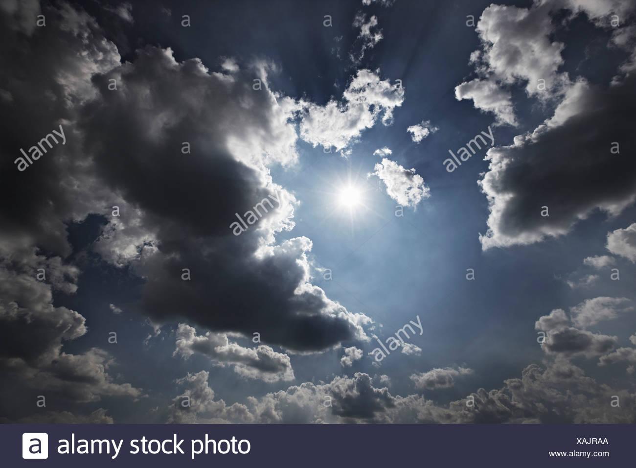 Sonne und Wolken am blauen Himmel Stockbild