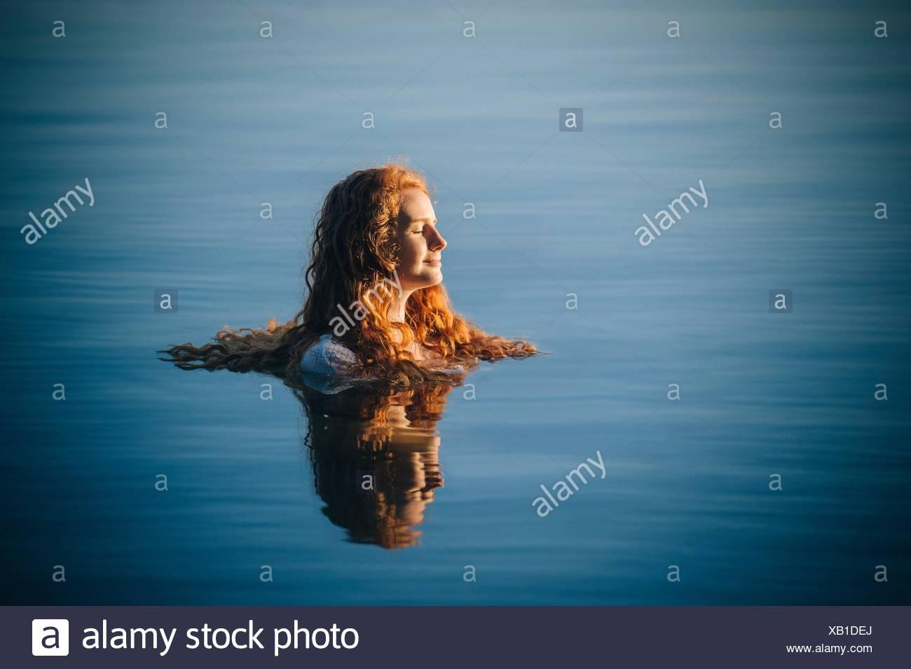 Kopf und Schultern der jungen Frau mit langen roten Haaren in See mit geschlossenen Augen Stockbild