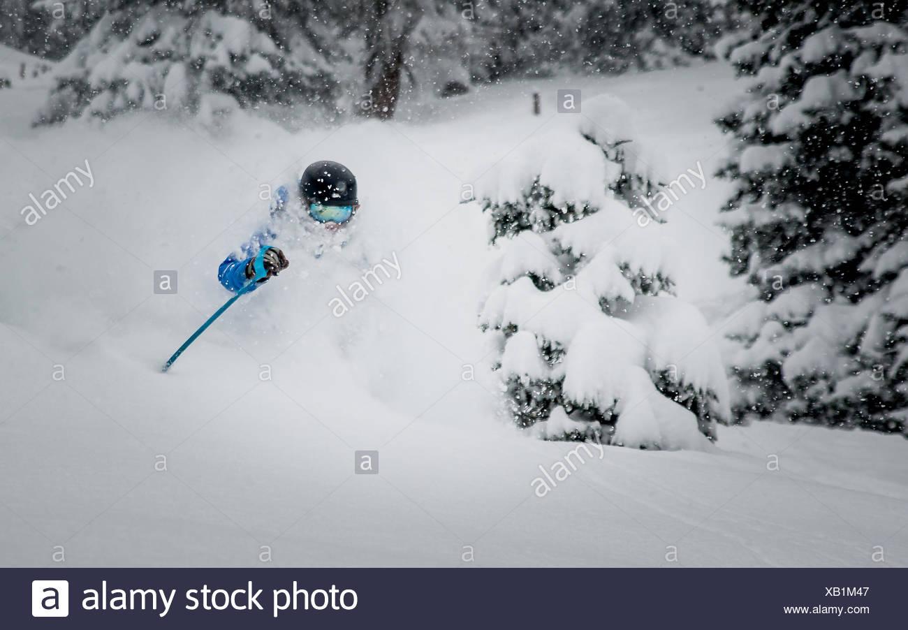 Ein männlicher Skifahrer Tiefschnee Skifahren in den österreichischen Alpen zu genießen. Stockbild