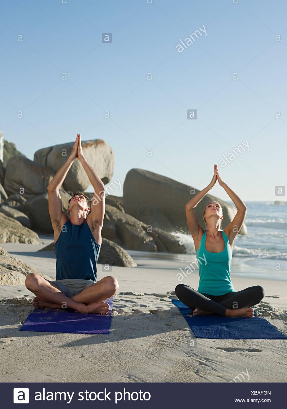 Junges Paar beim Yoga am Strand Stockbild