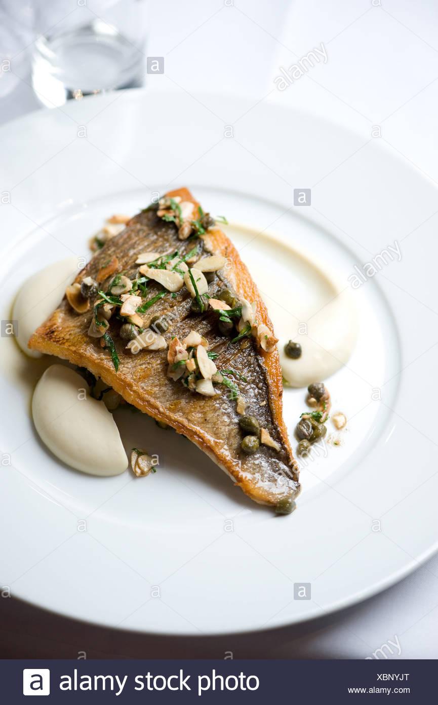 Fisch und Mandeln auf einem Teller Stockbild