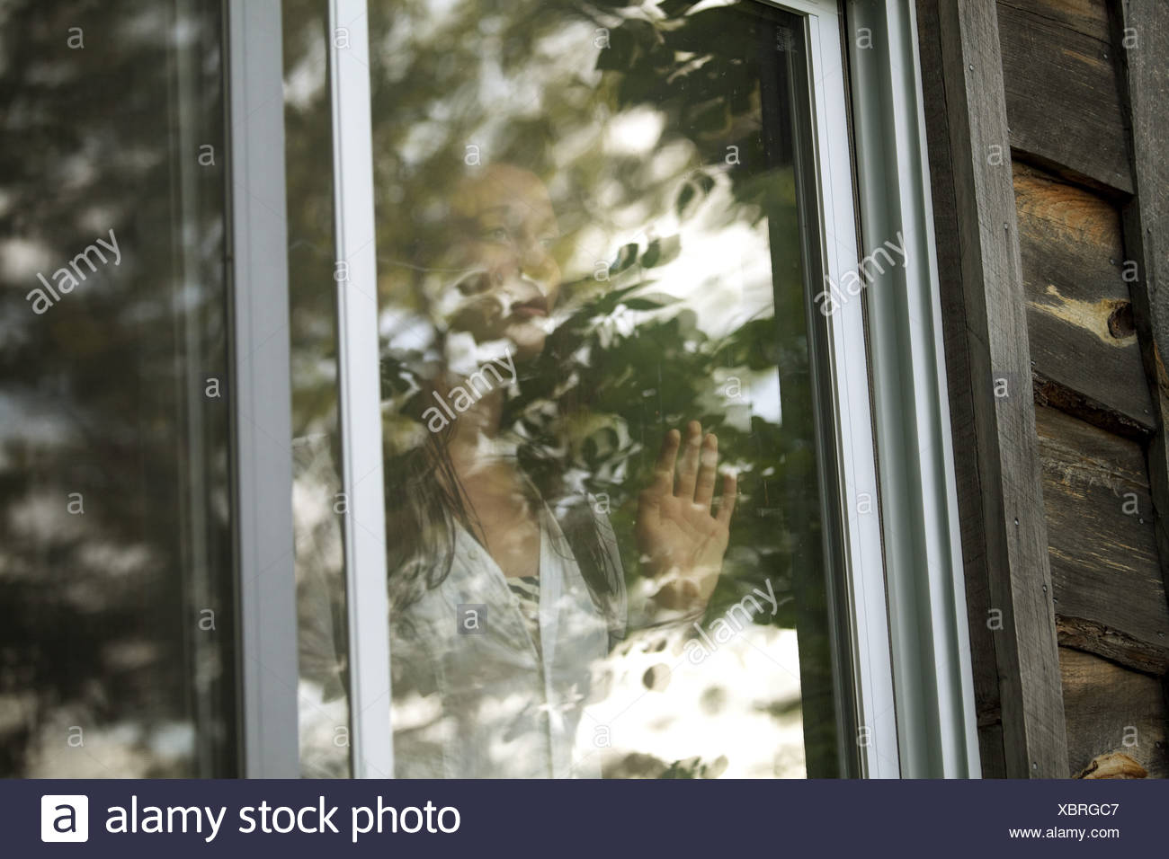 Teenager-Mädchen Blick durch Fenster Stockbild