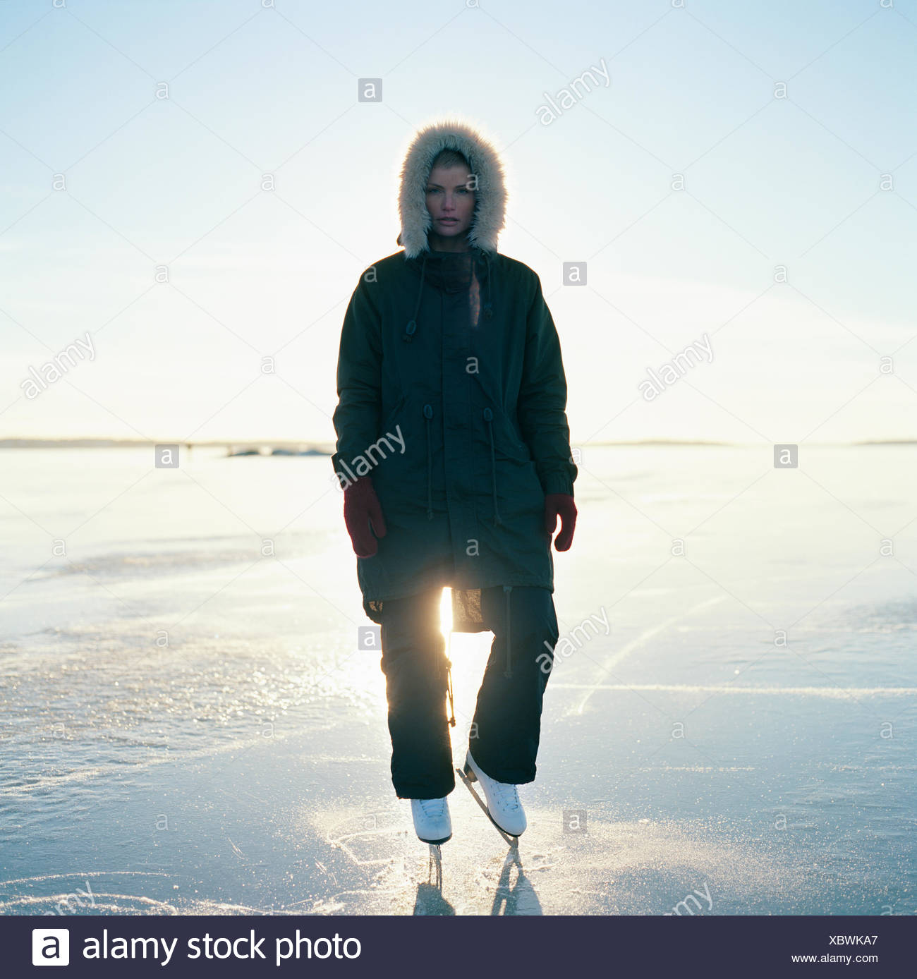 Schweden, Uppland, Varmdo, Bjorno, Mitte erwachsenen Frau in Schlittschuhe stehen auf zugefrorenen See Stockbild