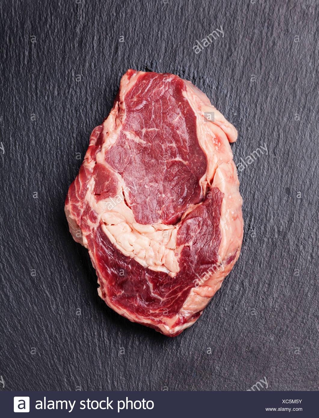 Rohes Frischfleisch auf dunklem Hintergrund Stockbild