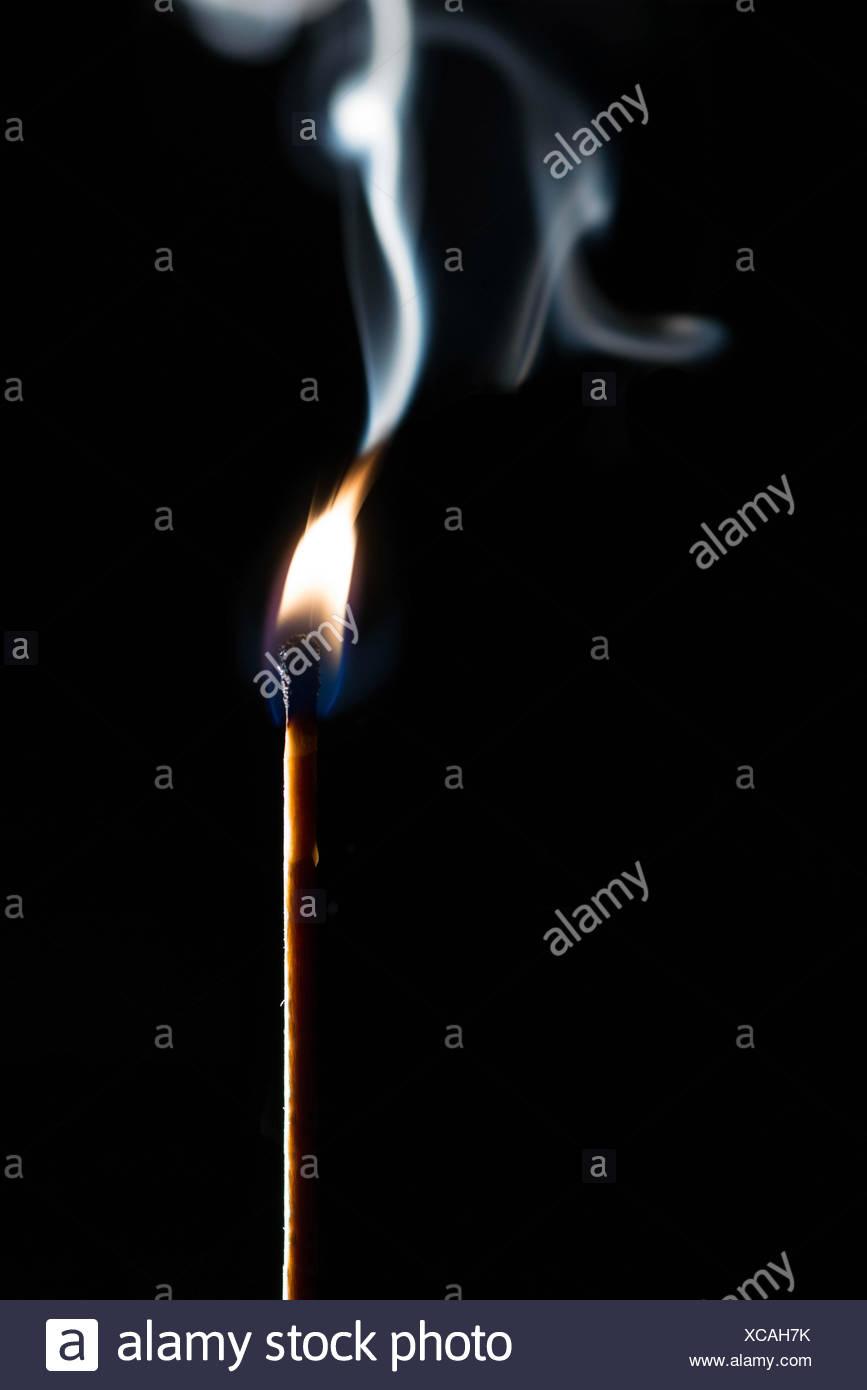 Gleichstock mit Rauch auf schwarzem Hintergrund Stockbild