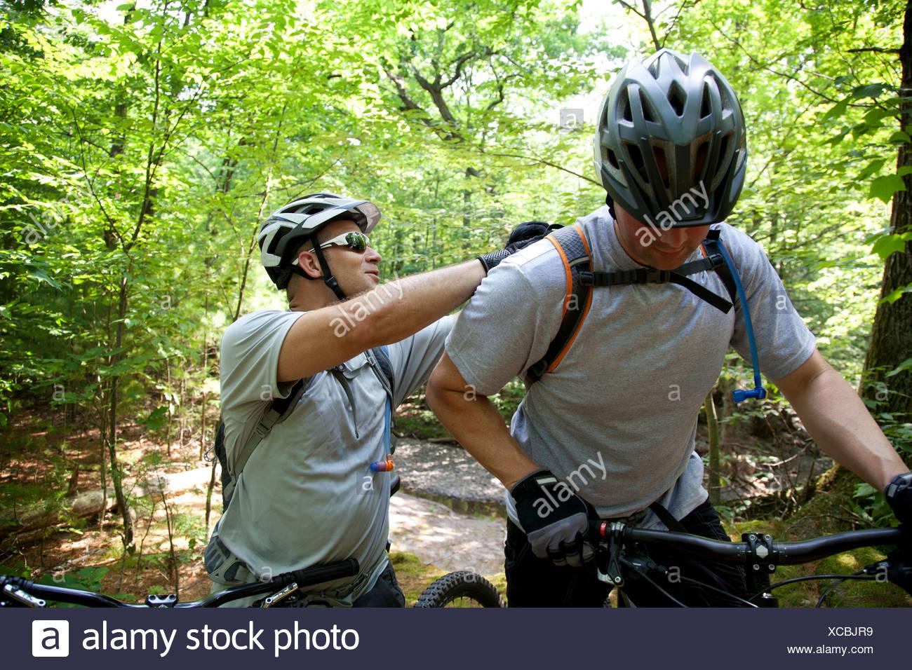 Mountainbiker, die Befestigung des Freundes Rucksack Stockbild