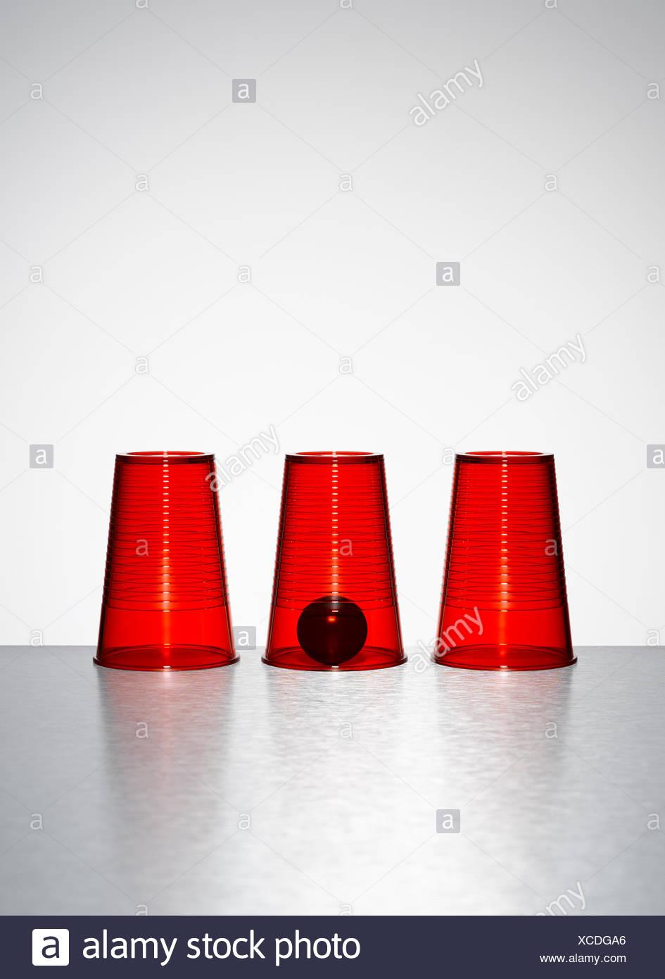 Ball unter mittleren von drei Tassen klares rot Stockbild