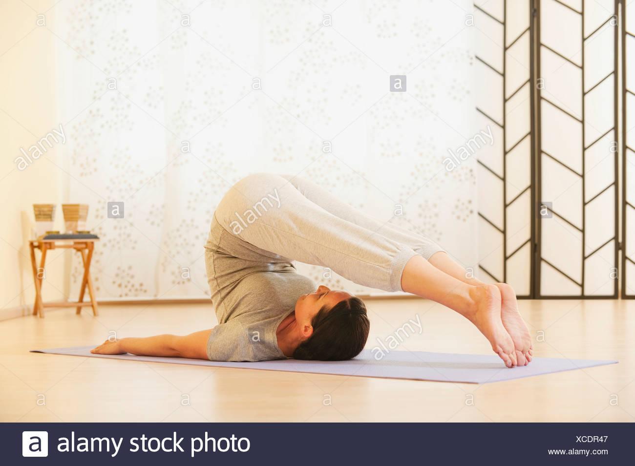 Frau, die Durchführung von Yoga auf Gymnastikmatte Stockbild