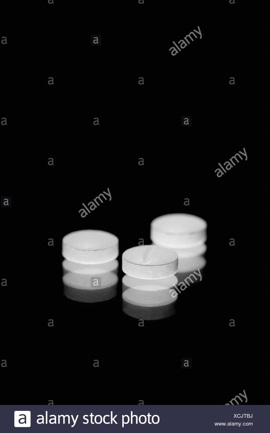 Weiße Tabletten auf einem schwarzen Hintergrund Stockbild