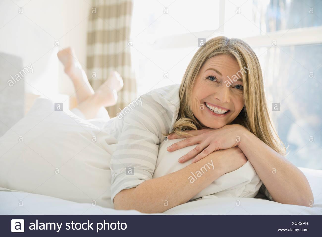Lächelnde Frau auf Bett Stockbild