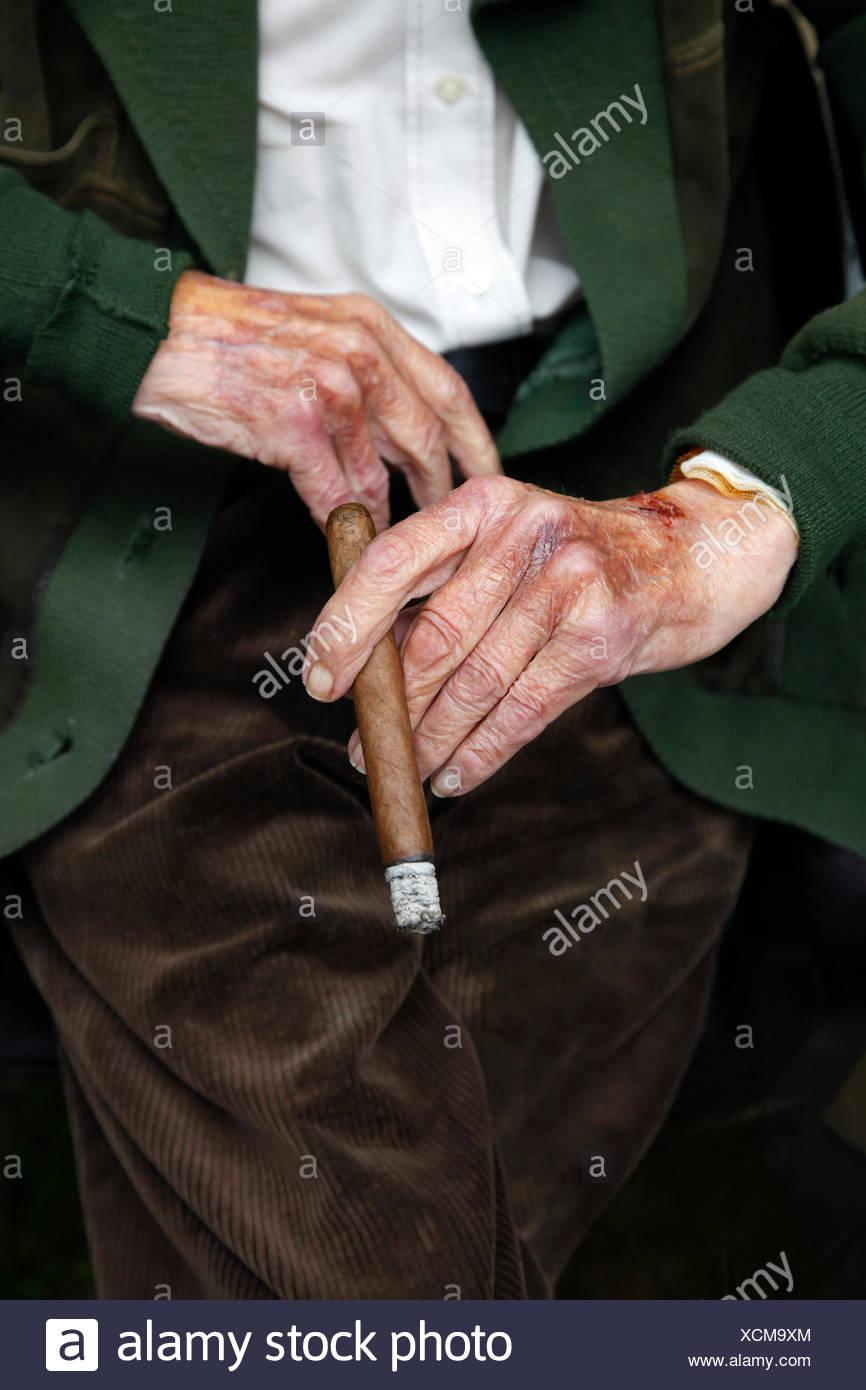 Händen der ein sehr alter Mann mit Zigarre, Cord Hose und Jacke, Seniorenheim, Berlin, Deutschland Stockbild