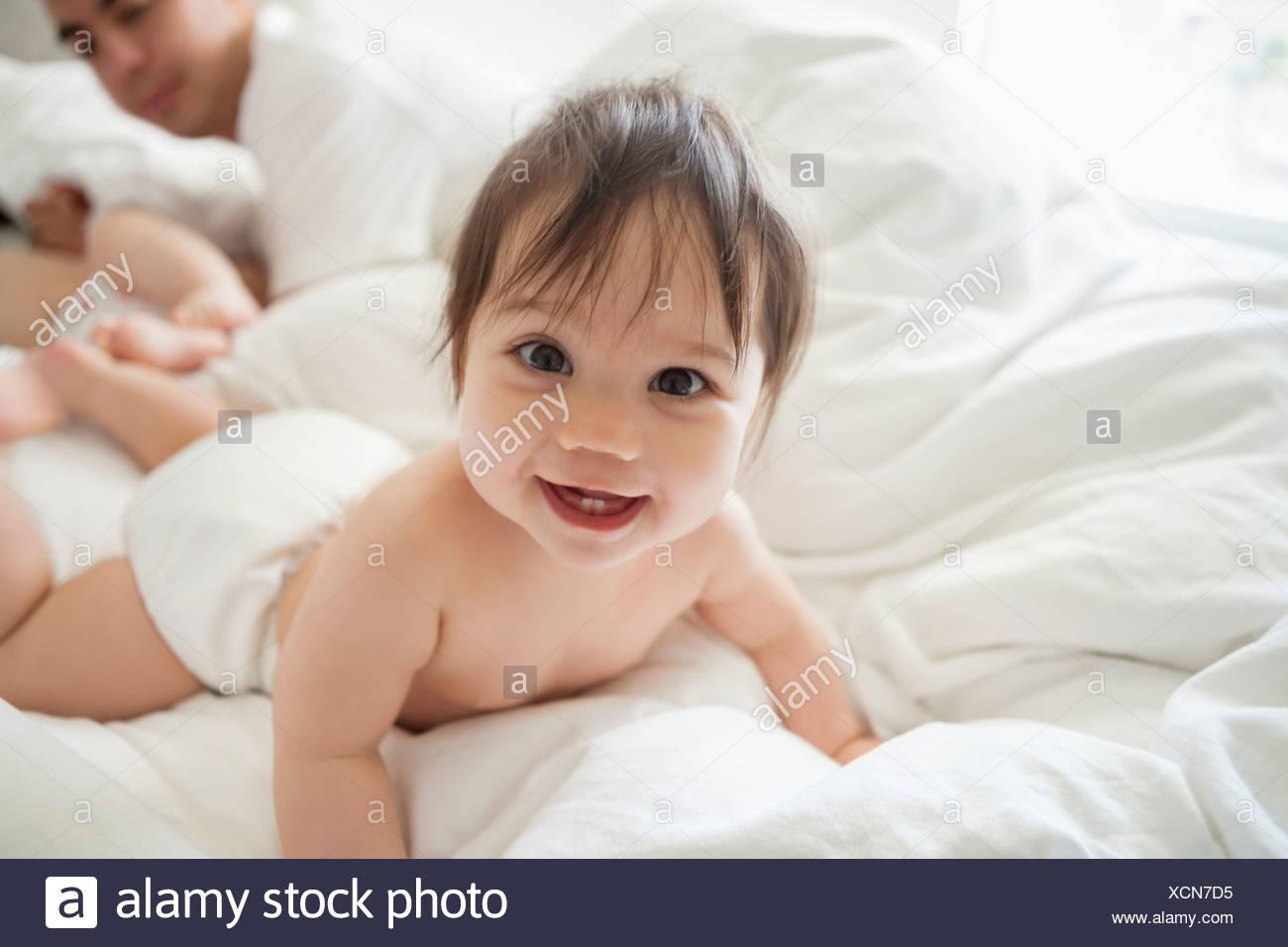 Babymädchen kriechen in Bettwäsche Stockbild