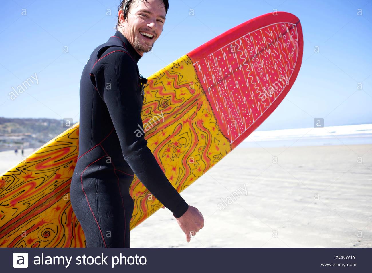 Männliche Surfer rennt auf dem Wasser während lächelnd. Stockbild