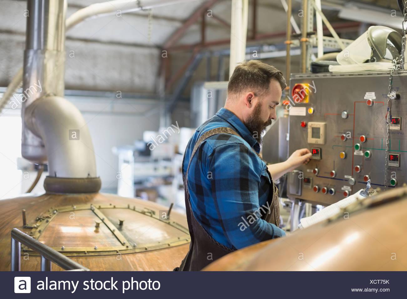 Brauerei-Arbeiter am Bedienfeld in der Nähe von Destillierapparaten aus Kupfer Stockbild