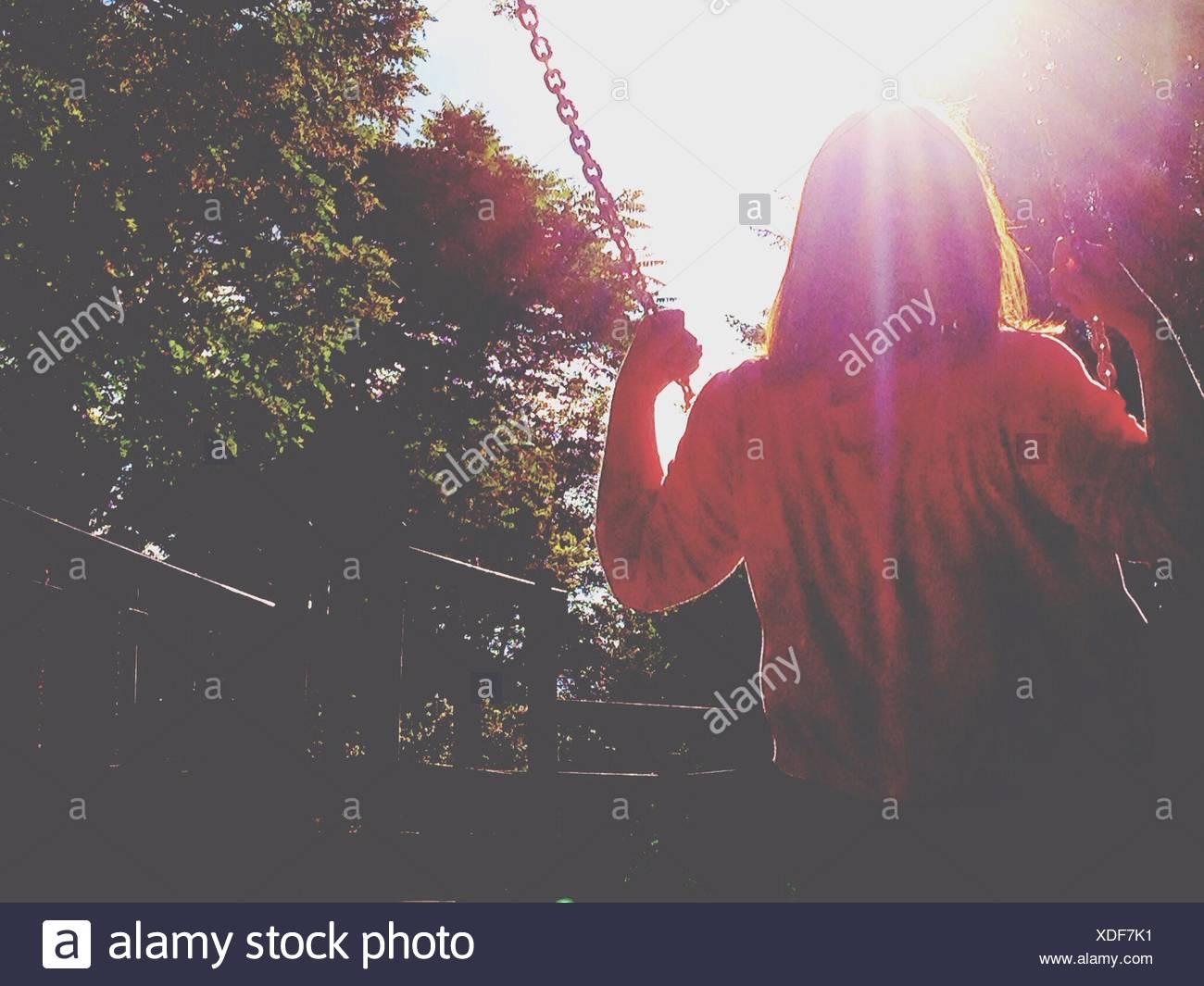 Rückansicht des Mädchen schwingen an sonnigen Tag Stockbild