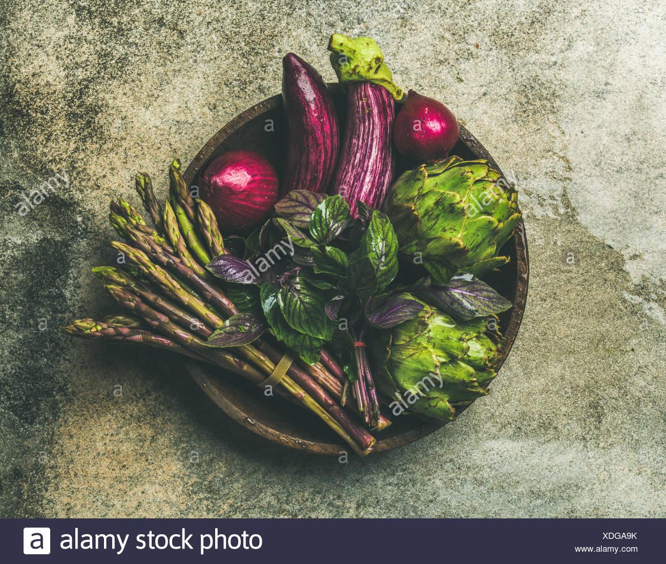 Flachbild-lay von Grün und Violett Gemüse auf der Platte über grauer Hintergrund, Ansicht von oben. lokale Produkte für gesundes Kochen. eggplans, Bohnen, Kohl, Spargel, Stockbild