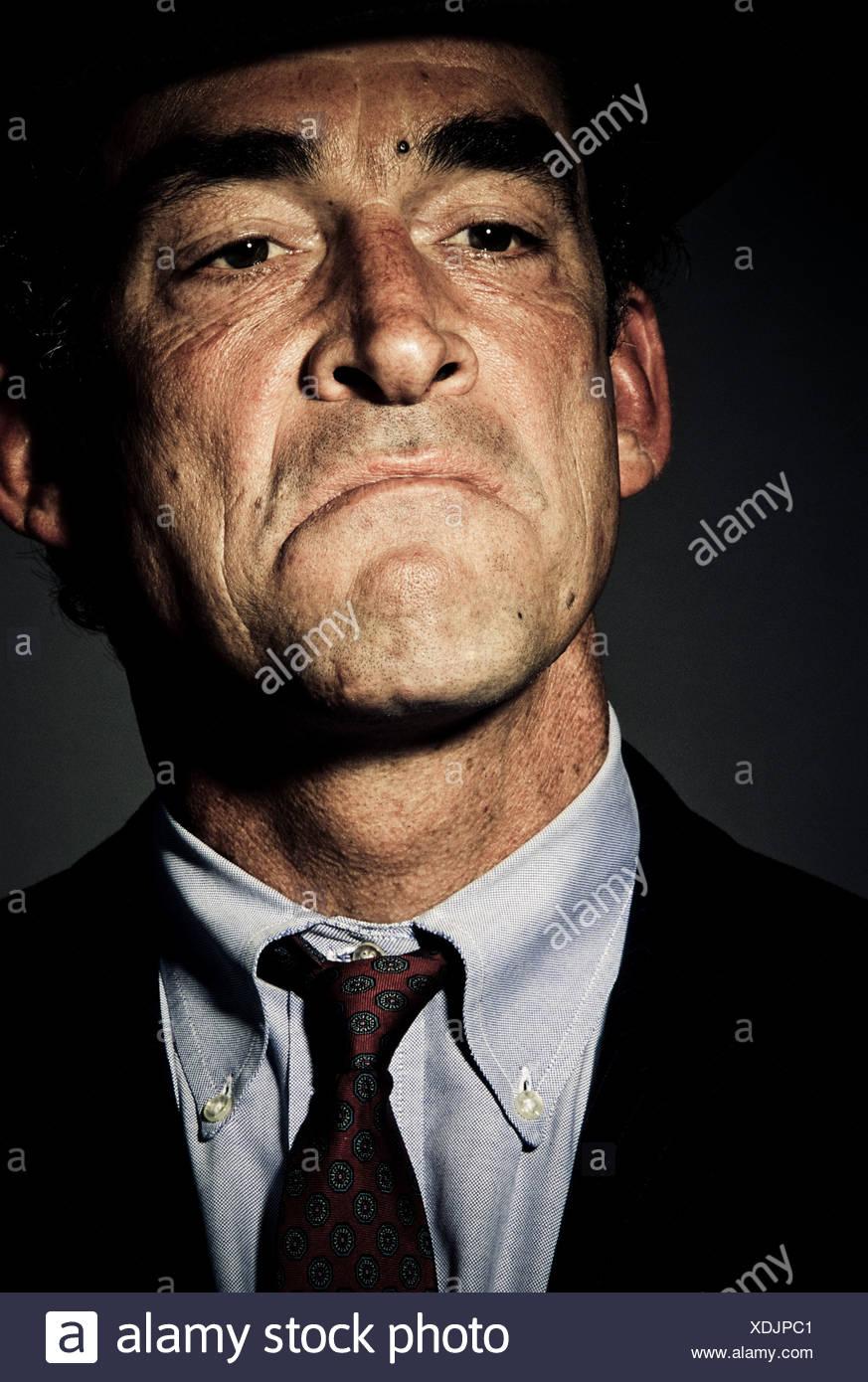 Niedrigen Winkel, Nahaufnahme, Frontansicht von einem reifen Mann im Anzug mit einem selbstgefälligen Ausdruck auf seinem Gesicht (Studio gedreht). Stockbild
