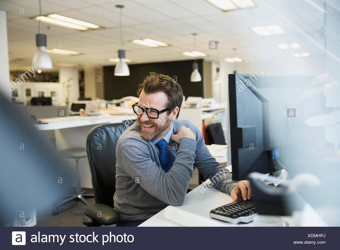 Geschäftsmann, arbeiten am Computer, die über Schulter lächelnd Stockbild