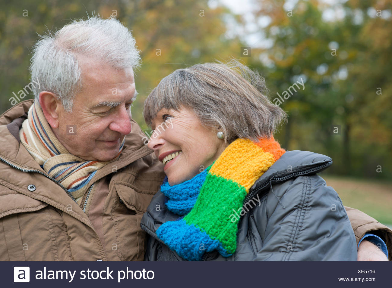 Älteres paar sitzen Arm in Arm auf einer Parkbank, lächelnd auf einander, Stadtpark, Berlin, Berlin, Deutschland Stockbild