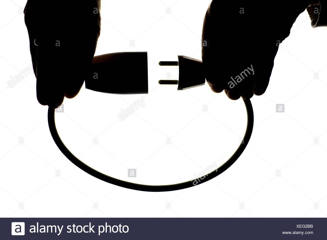 Nahaufnahme der Silhouette Hände halten Elektrokabel vor weißem Hintergrund Stockbild
