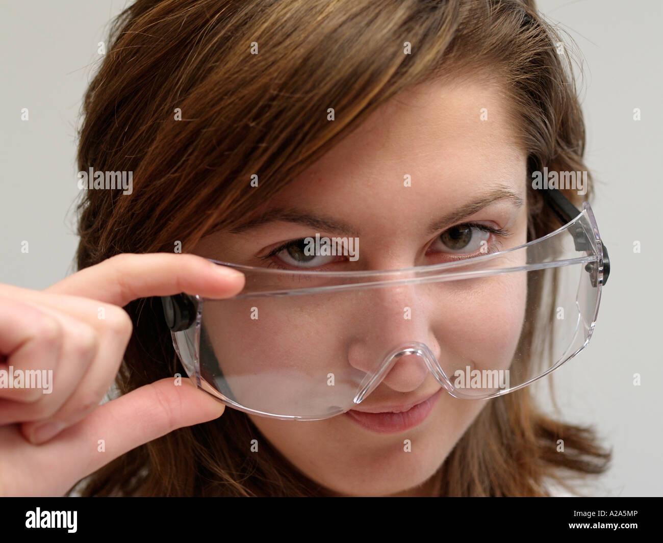 Mujer joven con twen mirar por encima de las gafas de seguridad ...