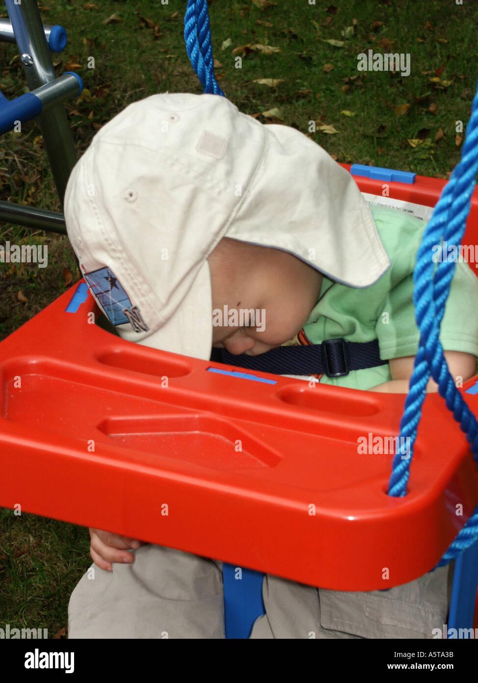 Pequeño niño dormido en un jardín rojo columpio vistiendo un ...