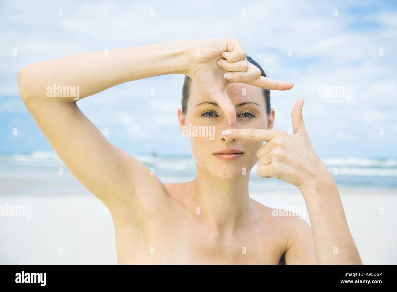 Mujer en la playa, haciendo dedo marco alrededor de los ojos, cabeza ...