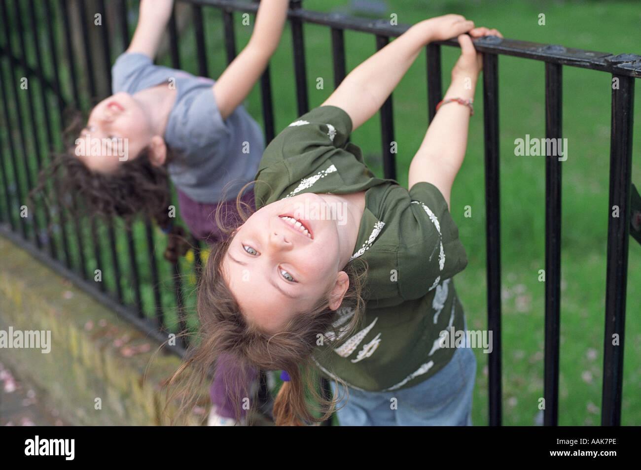 Dos niñas de seis años jugando en rejas metálicas, Londres, Reino Unido. Imagen De Stock