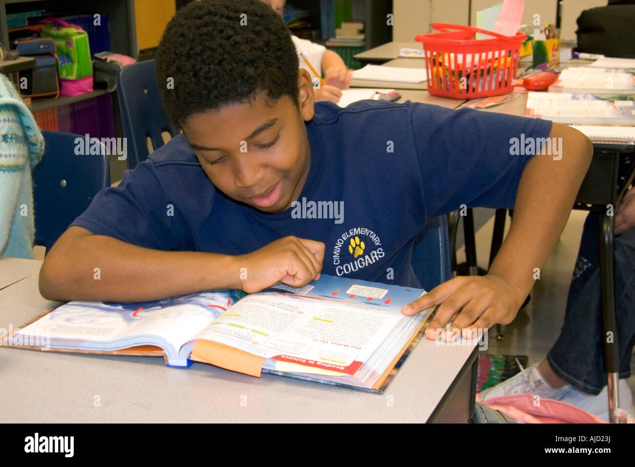 Estudiante de cuarto grado de primaria leyendo un libro en un aula ...