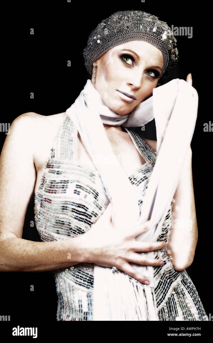 Joven mujer vistiendo el traje de noche de plata con sombrero y bufanda 9919ca59527d
