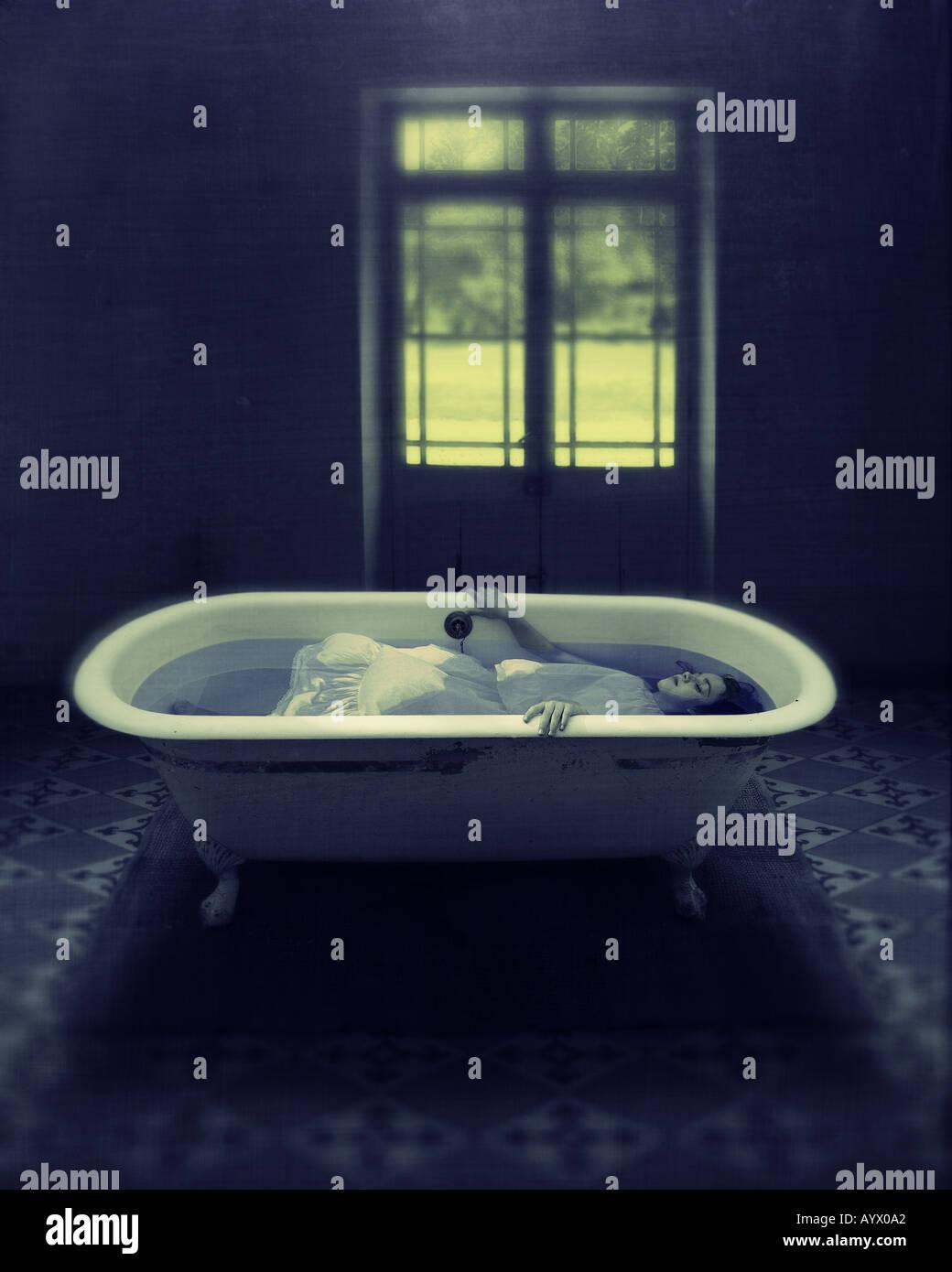Chica en vestido blanco sumergido en el agua en la bañera en la habitación vacía con una puerta al Imagen De Stock