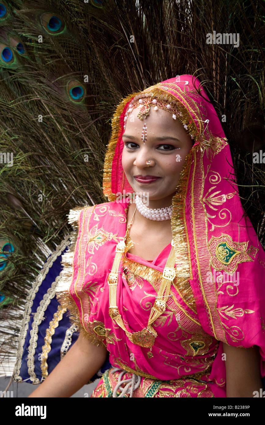 Mujer en el colorido traje Rajasthani abanicada con plumas de pavo ...