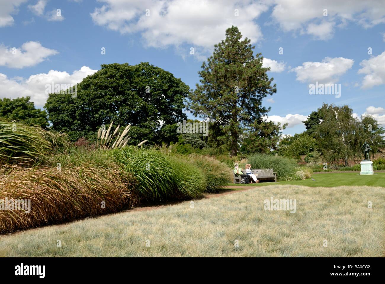 Los turistas sentados en un banco en el Real Jardín Botánico de Kew ...