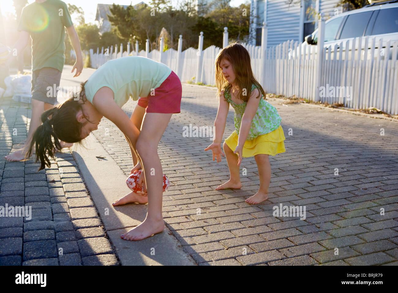 Dos niñas juegan al fútbol en un callejón con el sol en el fondo. Imagen De Stock