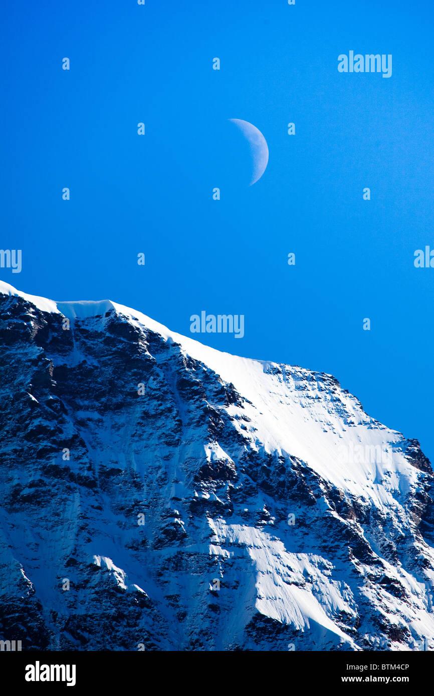 Un cuarto de luna se eleva sobre los Alpes Foto & Imagen De Stock ...